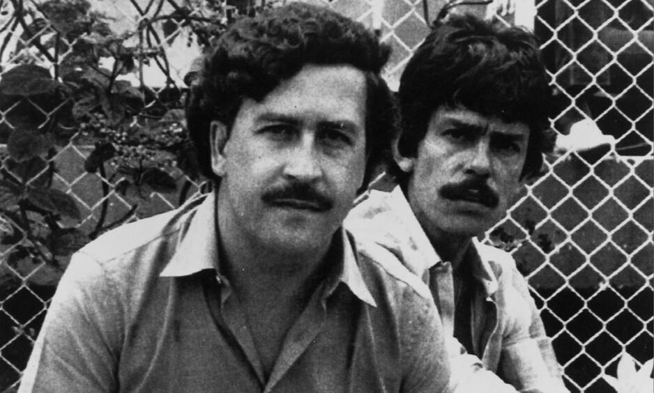 GLAD I FOTBALL: Her er narkobaron Pablo Escobar på en fotballkamp sammen med en ukjent mann. Han var veldig glad i sporten, og spyttet store summer inn i colombianske fotballklubber. Foto: AP Photo/NTB Scanpix