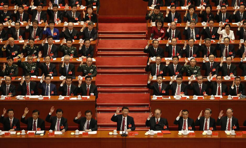 ENIGHET: Den kinesiske presidenten Xi Jinping ( i midten) fikk både navn og ideologi skrevet inn i Kinas grunnlov under kommunistpartiets 19. kongress. Her rekker medlemmene hendene i været under kongressens avsluttende seremoni. , Foto: AP Photo/Andy Wong/NTB Scanpix