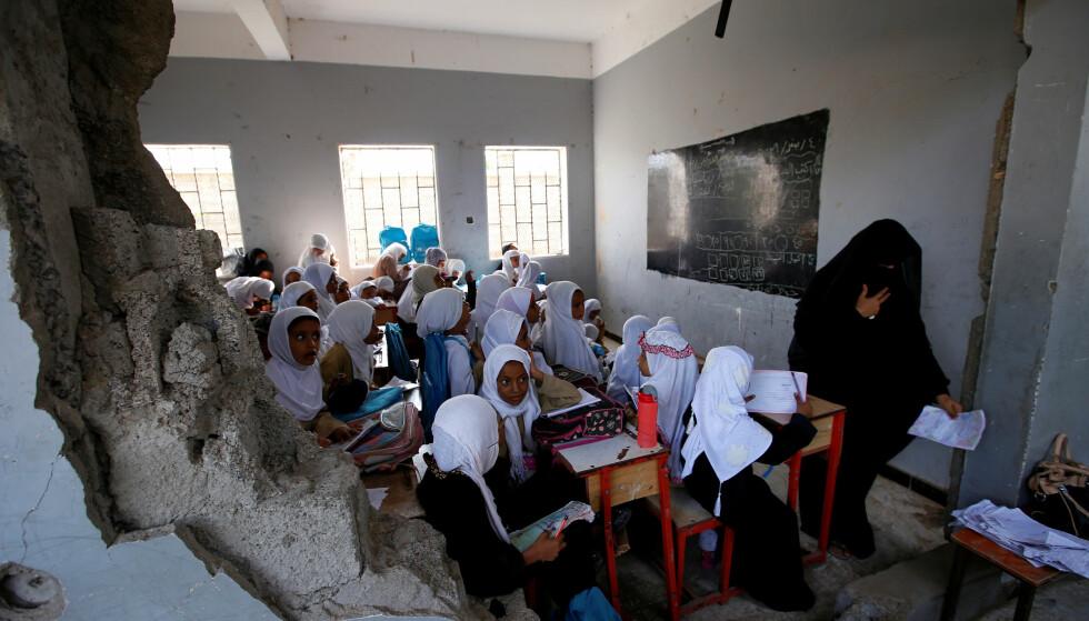 KRIGSFORBRYTELSER: En jenteklasse sitter i et klasserom som er delvis ødelagt etter et saudi-arabisk ledet angrep denne måneden. Alle parter som deltar i krigen i Jemen beskyldes stadig for brudd på humanitærretten, og for krigsforbrytelser. Foto: Abduljabbar Zeyad / Reuters / Scanpix