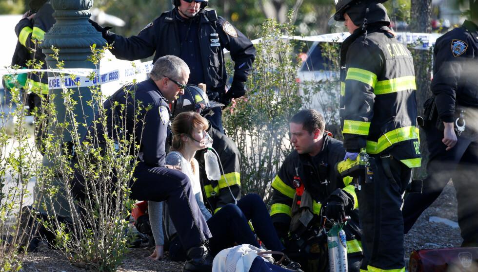 En kvinne blir tatt vare på av de første som ankom stedet. Foto: NTB Scanpix