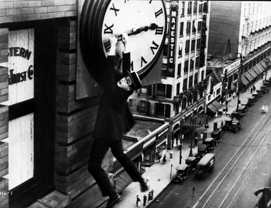 """HENGER I STROPPEN: Harold Lloyd i en berømt scene fra et av sine stumfilm-mesterverk, """"Safety Last"""". Her viser han med all mulig tydelighet hvordan mennesket bokstavelig talt slåss mot tiden. Foto: NTB Scanpix"""