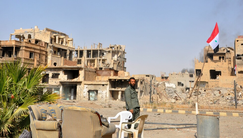 GJENEROBRET: Det syriske flagget vaier igjen over Deir az-Zor, men byen er totalt ødelagt. Foto: AFP/NTB Scanpix