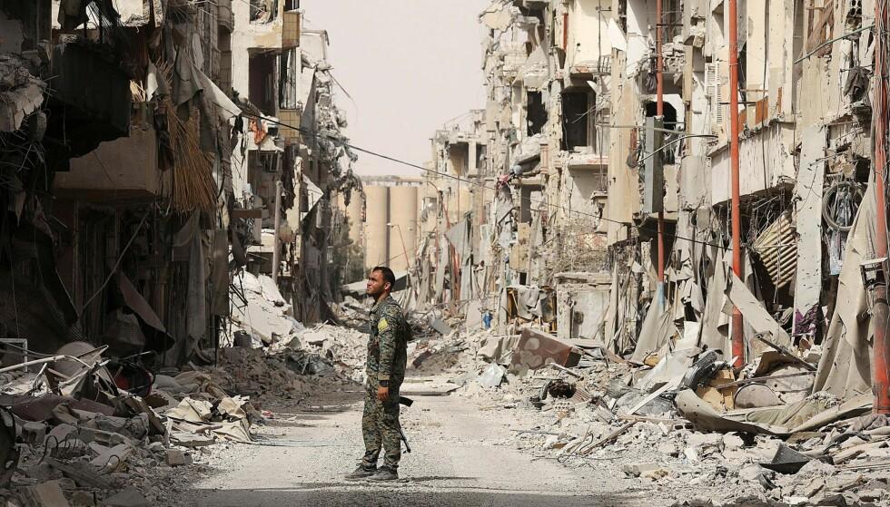 ENORME ØDELEGGELSER: En soldater for den såkalte syriske demokratiske hæren står i ruinene av Raqqa, byen som terrorgruppa IS kontrollerte inntil kort tid tilbake. Men kampene er langt fra over i Syria, og minst 50 personer mistet livet i helga. Foto: Erik De Castro / Reuters / Scanpix