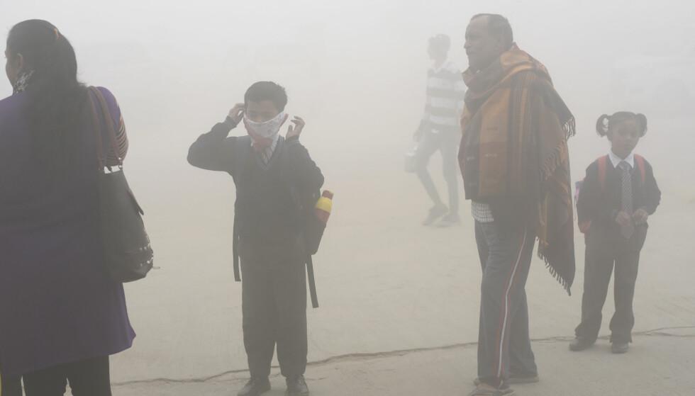 GIFTIG: En skolegutt i New Delhi prøver å beskytte seg mot den giftige smogen. Nå er 6000 skoler stengt på grunn av forurensning. Foto: AP Photo/R S Iyer