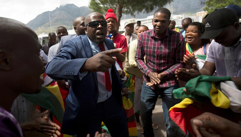 SYNGER UT: Flere av de oppmøte synger og feirer i gatene, etter at de har fått demonstrere fritt mot president Robert Mugabe. Foto: Rogan Ward