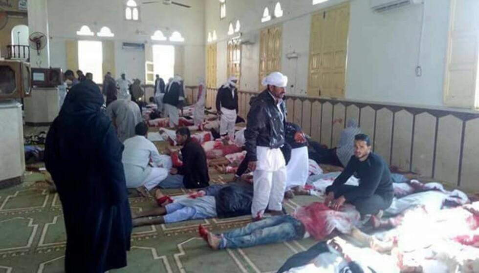 ANGREP: Folk sitter ved døde kropper etter angrep i Egypt. Hundrevis er døde og skadd etter en bombe gikk av. Foto: NTB Scanpix