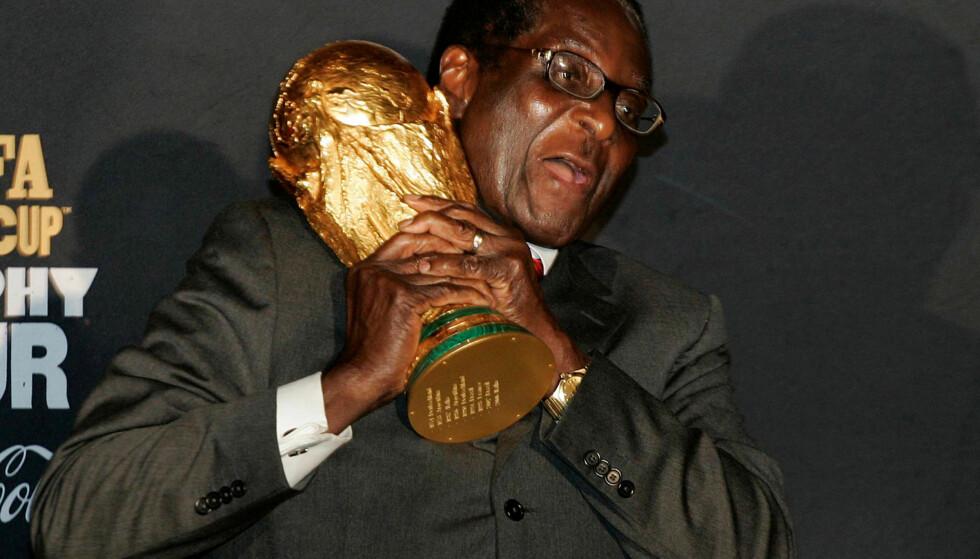 VM-TROFE: Robert Mugabe festet et solid grep om VM-trofeet på flyplassen i Harare i 2009. Det fikk han ikke beholde, men avgangen som president i Zimbabwe gjør ham ikke til en fattig mann. Foto: REUTERS / Philimon Bulawayo / NTB scanpix