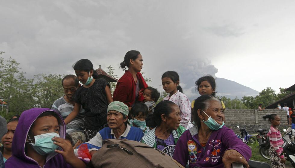 EVAKUERER: Her evakuerer innbyggerne med vulkanen i bakgrunnen. Bildet er tatt for to dager siden. Foto: AP Photo/Firdia Lisnawati
