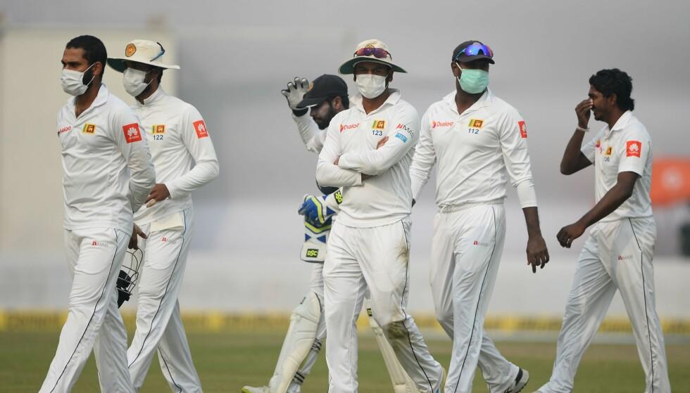 BAR STØVMASKER: Søndagens kamp mellom Sri Lanka og India ble flere ganger avbrutt av at spillerne måtte kaste opp på grunn av luftforurensningen, til tross for at Sri Lankas cricketlag bar støvmasker. Foto: AFP photo / Sajjad Hussain / NTB Scanpix