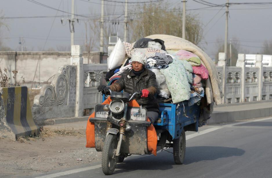 HUSLØS: En migrantarbeider i Beijing har lastet opp alle eiendelene på motorsykkel for å dra hjem til provinsen. Etter en dødelig brann har byen lansert en kampanje der migrantenes boliger raseres og folk settes på gata over natta. Foto: Reuters / NTB Scanpix