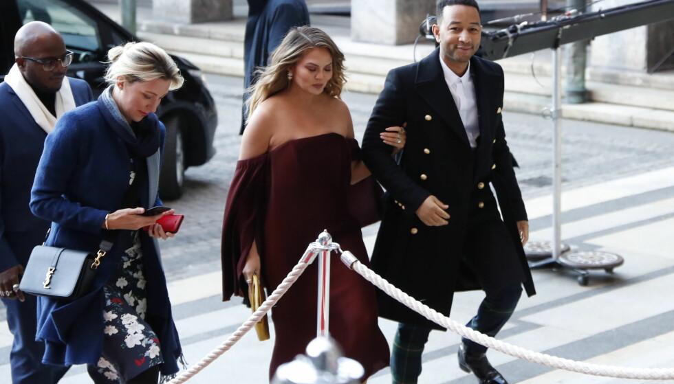 GLAM: Chrissy Teigen og John Legend er i Oslo denne helgen. Chrissy hadde på seg en rød, skulderkjole, mens ektemannen hadde på seg en kåpe i Balmain-stil. Foto: NTB scanpix