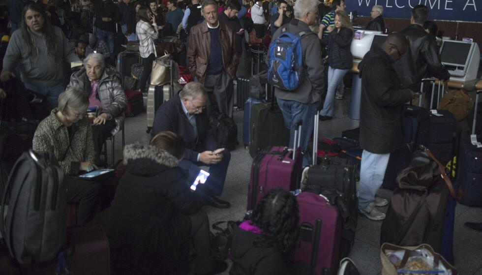 I MØRJET: Her venter passasjerer inne i den mørklaget terminalbygningen. Hatsfield-Jackson-flyplassen var uten trøm i timesvis søndag. Foto: Steve Schaefer / Atlanta Journal-Constitution via AP / NTB scanpix