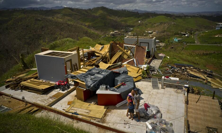 ØDELAGT HJEM: Her står en puertoricansk familie foran sitt ødelagte hjem. Nå - tre måneder etter Marias herjinger - er fortsatt flere uten strøm. Foto: Ramon Espinosa / AP / NTB Scanpix