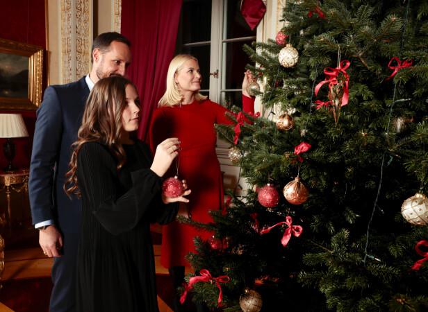 PYNTER JULETRE: Kronprinsesse Mette-Marit, kronprins Haakon og prinsesse Ingrid Alexandra pynter juletreet på Slottet. Foto: Lise Åserud / NTB scanpix