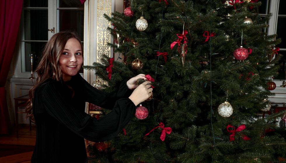 SÅNN PASSE HØYT SKAL DEN HENGE: Prinsesse Ingrid Alexandra sørger for at julekulene får riktig plass på juletreet. Foto: Lise Åserud / NTB Scanpix