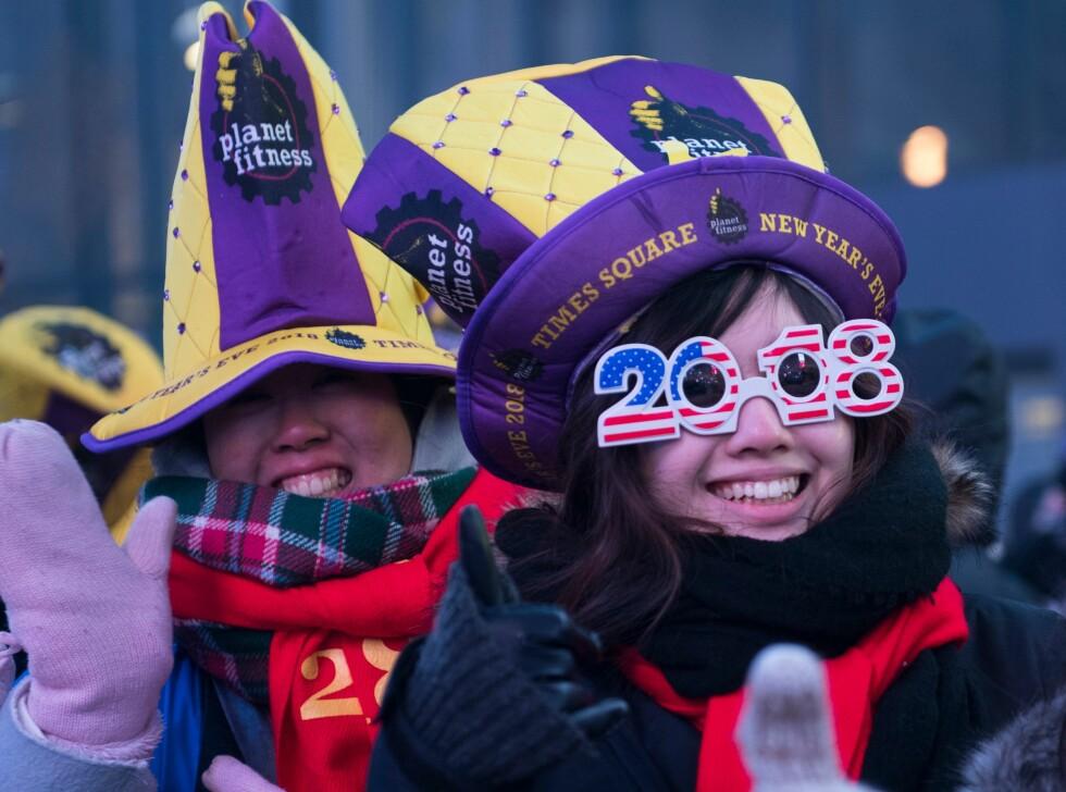 BRILLEFIN: Hatter og briller valgt ut for anledningen, på noen av de oppmøtte på Times Square i New York. Foto: AFP PHOTO / DON EMMERT