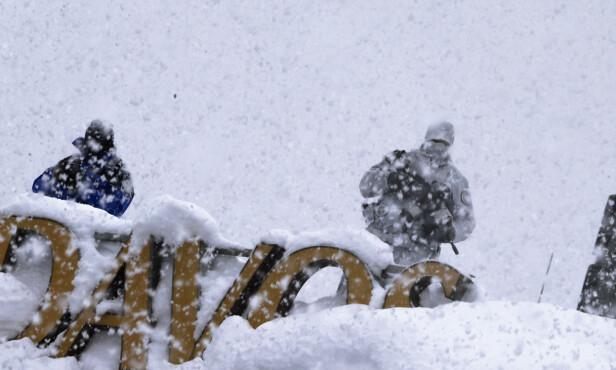 BEVÆPNET: Sikkerheten står i høysetet når flere av verdens mektigste ledere og rikeste personer samles til World Economic Forum i Davos. Jobben er ikke bare hyggelig for sikkerhetspolitiet i den sveitsiske alpebyen, som det siste døgnet har fått oppleve det kraftigste snøfallet på 20 år. Foto: Markus Schreiber / AP / NTB Scanpix