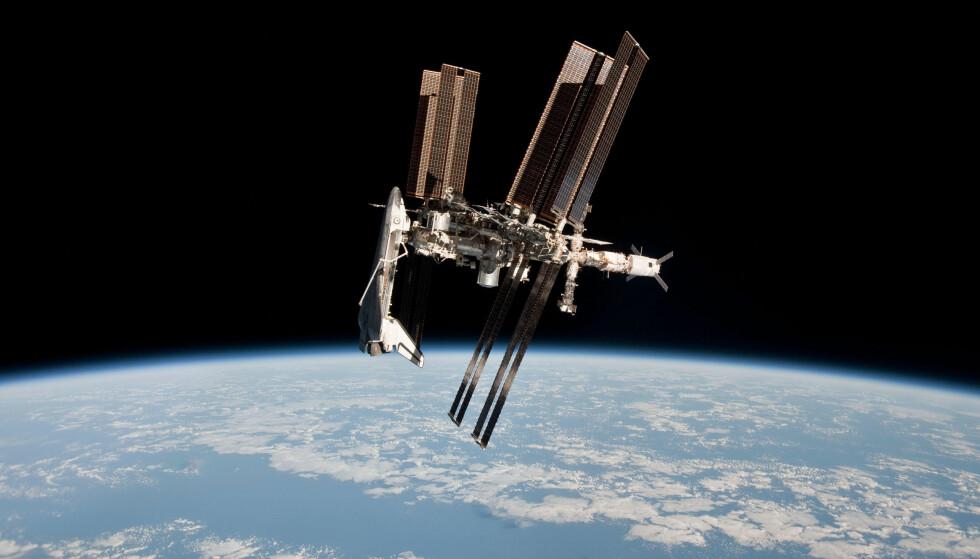 SYNLIG FRA JORDA: Den internasjonale romstasjonen (ISS) er godt synlig fra jorda dersom man vet hvor blikket skal rettes. Her i 2011, med romferja «Endeavour» koblet til. Foto: Nasa / AFP / NTB Scanpix
