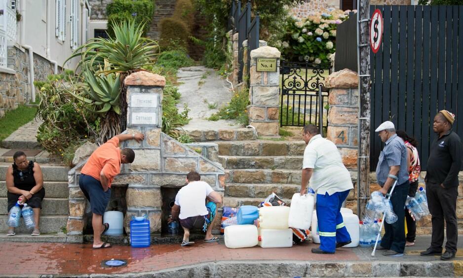 LANGE KØER: Folk i Cape Towns forsteder står allerede i lange køer for å få ekstra vann. Foto: AFP PHOTO / RODGER BOSCH