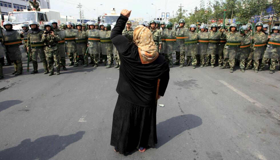 MOTSTAND: Muslimsk kvinne protesterer mot nærværet av kinesisk opprørspoliti i Urumqi, hovedstaden i den uigur-dominerte Xinjiang-regionen vest i Kina. Foto: Reuters / NTB Scanpix