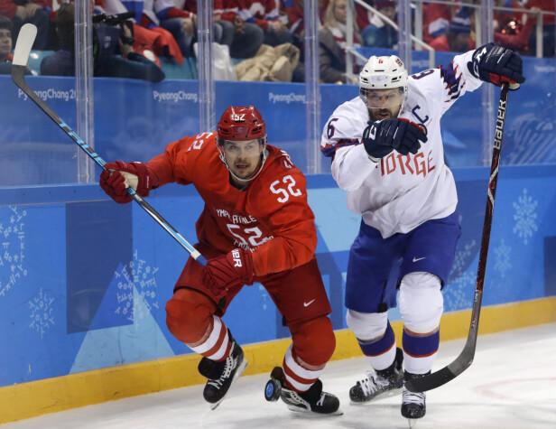 HANG IKKE MED: Den norske landslagskapteinen Jonas Holøs (t.h) i duell mot russiske Sergei Sjirokov i OL-kvartfinalen i ishockey tirsdag morgen. Foto: David W. Cerny / Reuters / NTB Scanpix