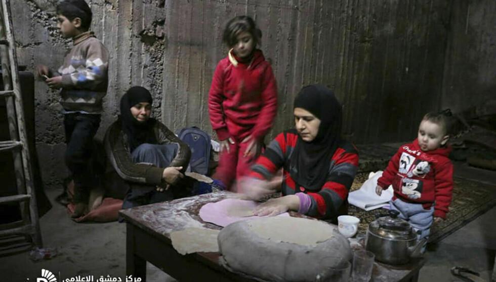 STOR NØD: Bildet viser en syrisk kvinne som baker brød i et bomberom i Øst-Ghouta, utenfor Damaskus. Foto: Syrian Damascus Media Center / AP / NTB Scanpix