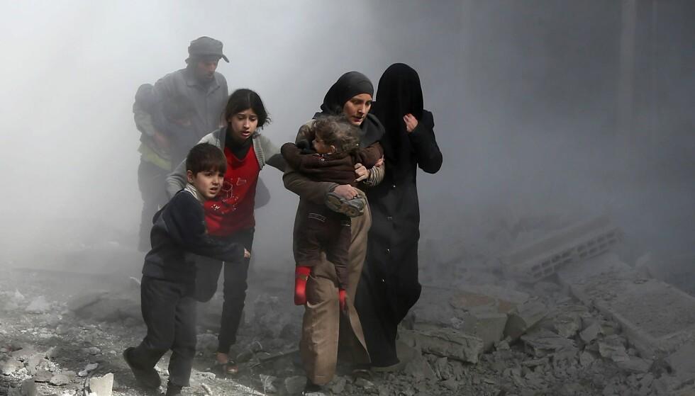 PÅ FLUKT FRA BOMBEREGNET: Slik så det ut i den opprørskontrollerte byen Jisreen i Øst-Ghouta sist torsdag mens syriske fly fortsatte sine nådeløse angrep. Foto: Abdulmonam Eassa/AFP/NTB Scanpix