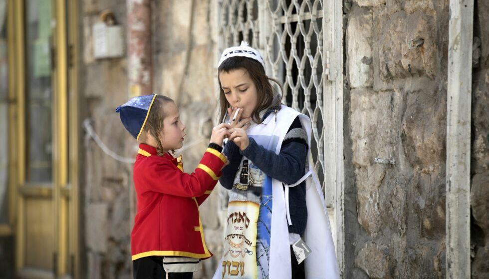 EN BLÅS MELLOM SLAGENE: Jødene har akkurat feiret høytida Purim. Her er to ultra-ortodokse barn i Jerusalem, utkledd for anledningen. Foto: NTB Scanpix / EPA / Atef Safadi
