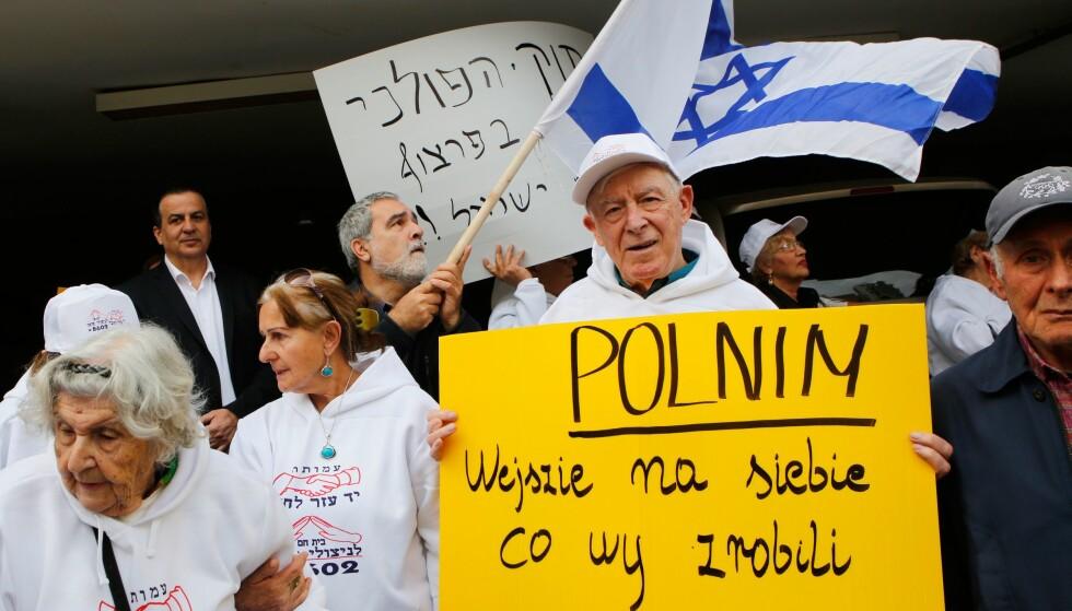 MOT NY LOV: Holocaust-overlevere demonstrerer foran Polens ambassade i Tel Aviv mot den kontroversielle loven som begrenser omtalen av dødsleirene i Polen. Foto: AFP / NTB Scanpix