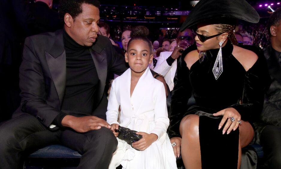 BLADDE OPP: Seks år gamle Blue Ivy Carter, her fotografert mellom de verdenskjente foreldrene sine, slo på stortromma på en auksjon denne helga. Hun brukte hele 10 000 dollar, nærmere 77 000 kroner, på en skulptur. Hun var også nære å bruke 19 000 dollar på et maleri. Foto: NTB scanpix