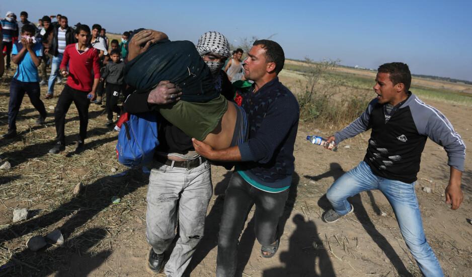 RETUR-MARSJ: Fredag var rundt 30 000 palestinere i nærheten av grensa mellom Gaza og Israel for å markere starten på en seks uker lang «retur-marsj». 15. mai feirer Israel at det er 50 år siden uavhengighetserklæringen til Israel, samtidig som palestinere vil markere al-Nakba, katastrofen, der 700 000 palestinere ble tvunget på flukt. På bildet blir en palestinsk mann båret bort etter å ha blitt skadd i sammenstøt med israelske tropper i Khan Younis i går. Foto: Shutterstock / Scanpix