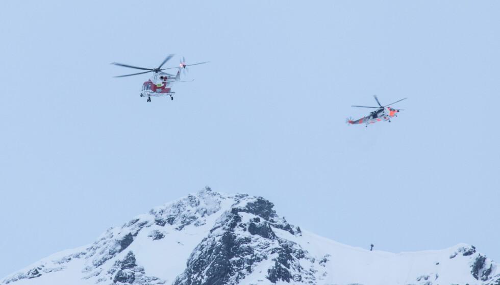 VANSKELIGE FORHOLD: Både ambulansehelikopter og Sea King redningshelikopter deltok i redningsaksjonen etter snøskredet i Sydalsfjellet i Lofoten første påskedag. En mann er bekreftet omkommet etter å ha blitt tatt av skredet. Foto: Eric Fokke / NTB scanpix