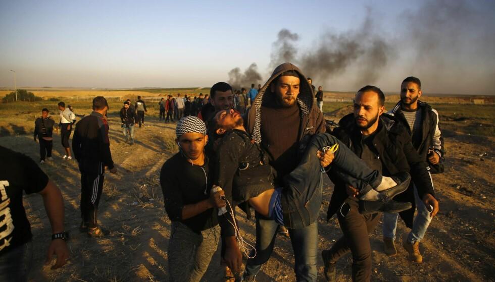 SÅRET: Palestinske demonstranter bærer en skadet kamerat. Foto: AFP / NTB Scanpix