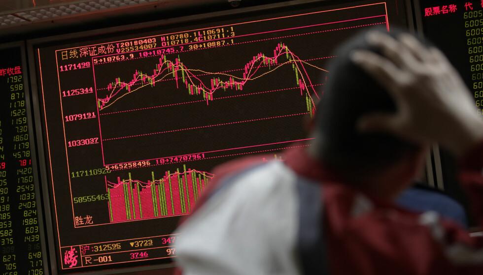 FALL: USA opplevde i går store børsfall, noe som ble fulgt opp på børsene i Asia. Oslo børs følger etter med røde tall ved handelsstart tirsdag. Foto: AP Photo/Andy Wong/NTB Scanpix