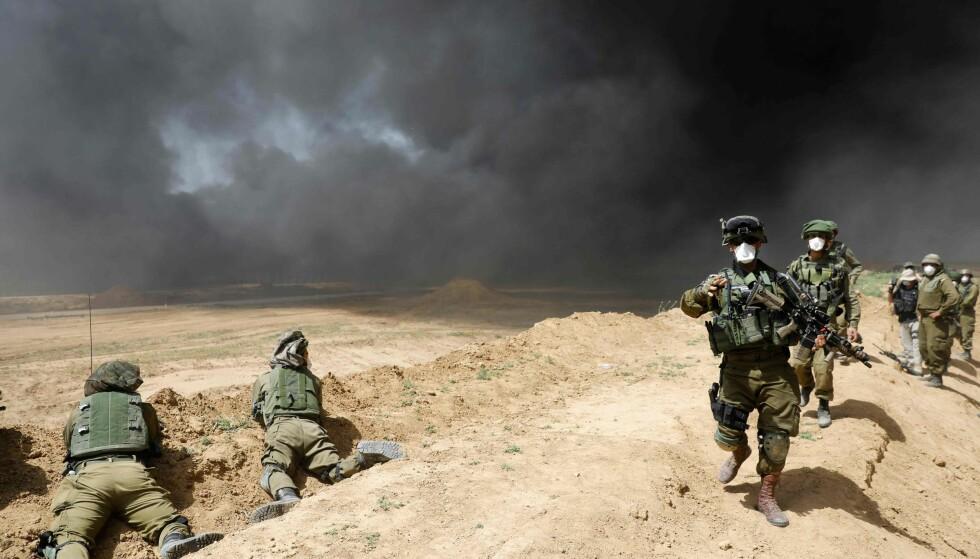 GAZA: Isaelske styrker oppholder seg på grensen mellom Israel og Gaza. Fredag ble en palestinsk fotograf skutt og drept. Foto: AFP PHOTO / MENAHEM KAHANA
