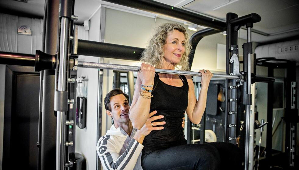 5 FØR 50: Målet da Trine Horneland Boilesen startet å trene styrke for et år siden, var å greie fem chin-ups før hun fylte 50 år. Da hun startet, greide hun ingen. Forrige uke fylte hun 50. Og hun tar lett fem chin-ups– kroppsheving i bom med underhåndsgrep. Her med personlig trener Henrik Westgaard. Foto: Bjørn Langsem