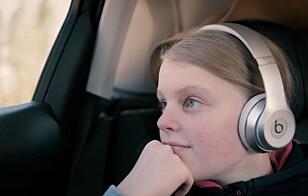 UNNGÅ BILSYKE: Med hodetelefoner kan Oda (13) høre på sin egen lydbok uten å forstyrre resten av familien.