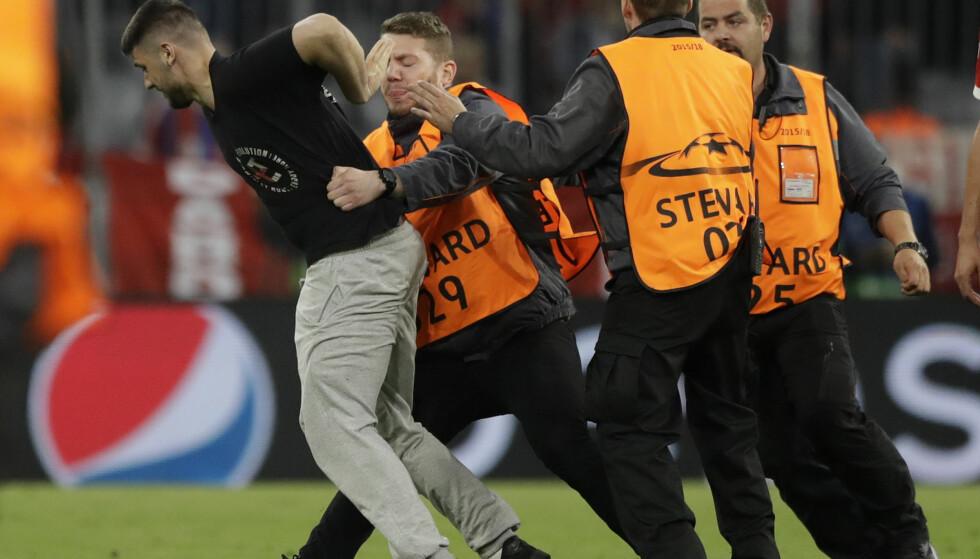 STORMET BANEN: Flere supportere stormet banen etter gårsdagens kamp mellom Bayern Munchen og Real Madrid. Foto: NTB Scanpix