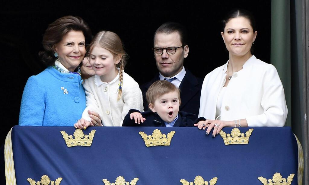 ABLEGØYER: Dronning Silvia, prinsesse Sofia (i bakgrunnen t.v.), prinsesse Estelle, prins Oscar, prins Daniel og kronprinsesse Victoria sammen på slottsbalkongen i Stockholm mandag - men det var ingen tvil om hvem som fikk mest oppmerksomhet. Foto: Karin Törnblom /IBL/ NTB scanpix