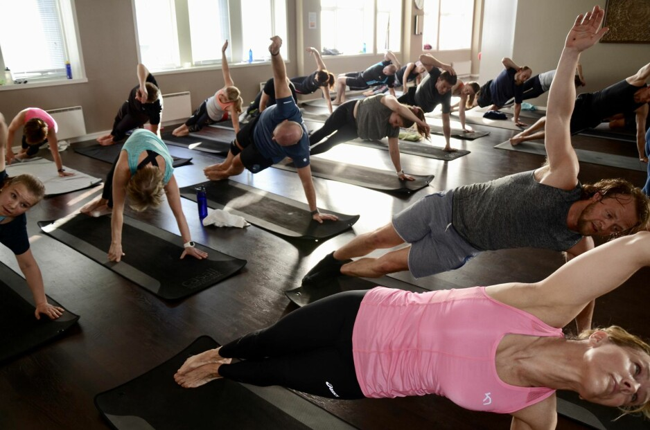 ALLE KAN DELTA: - Det fine med denne yogatimen er at alle kan delta, og føle at de mestrer øvelsene uten noen form for tidligere yogaerfaring. Det minsker terskelen for å slenge seg på, og jeg opplever at folk kommer igjen og igjen. Mange av dem er menn. Det er gøy, sier instruktør Clarissa Bergh. Foto: Kristin Roset