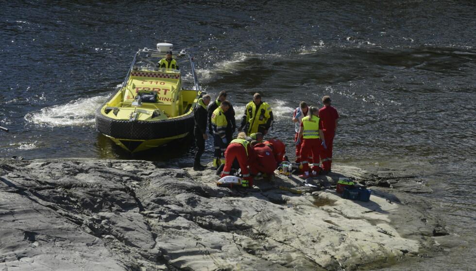 LIVREDDENDE FØRSTEHJELP: To personer er fraktet til sykehus etter å ha blitt tatt av strømmen i Nidelva. Her mottar en av mennene livreddende førstehjelp på stedet. Foto: Joakim Halvorsen