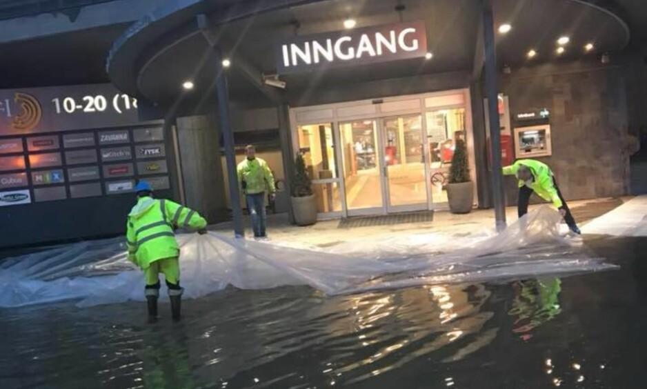 STENGT: På Otta hadde Gudbrandsdalslågen steget så mye at parkeringsplassen ligger under vann ved kjøpesenteret Amfi. Nå risikerer man at vannet flommer inn hovedinngangen til kjøpesenteret. Foto: Amfi Otta / Facebook