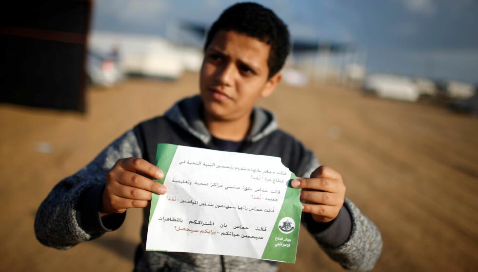 FLYGEBLAD: En innbygger på Gaza holder flygebladet IDF har sluppet over det palestinske området, der de oppfordrer innbyggerne til å forholde seg rolige i dag. Foto: Mohammed Salem / Reuters / NTB Scanpix