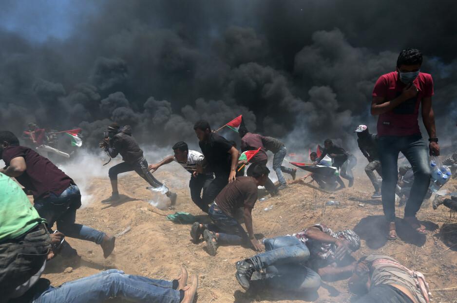 VOLDSOMME PROTESTER: Rundt 35 000 palestinere skal være med på dagens demonstrasjon ved grensa til Israel i Gaza. Her løper palestinere for å komme unna tåregassen og kulene som israelske skarpskyttere skyter mot dem. Foto: Ibraheem Abu Mustafa / Reuters / Scanpix