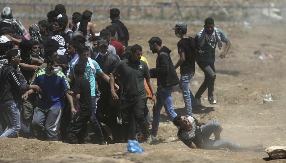 DEMONSTRASJON: En palestinsk demonstrant faller til bakken etter å ha blitt truffet av israelske kuler. Foto: AP / NTB scanpix