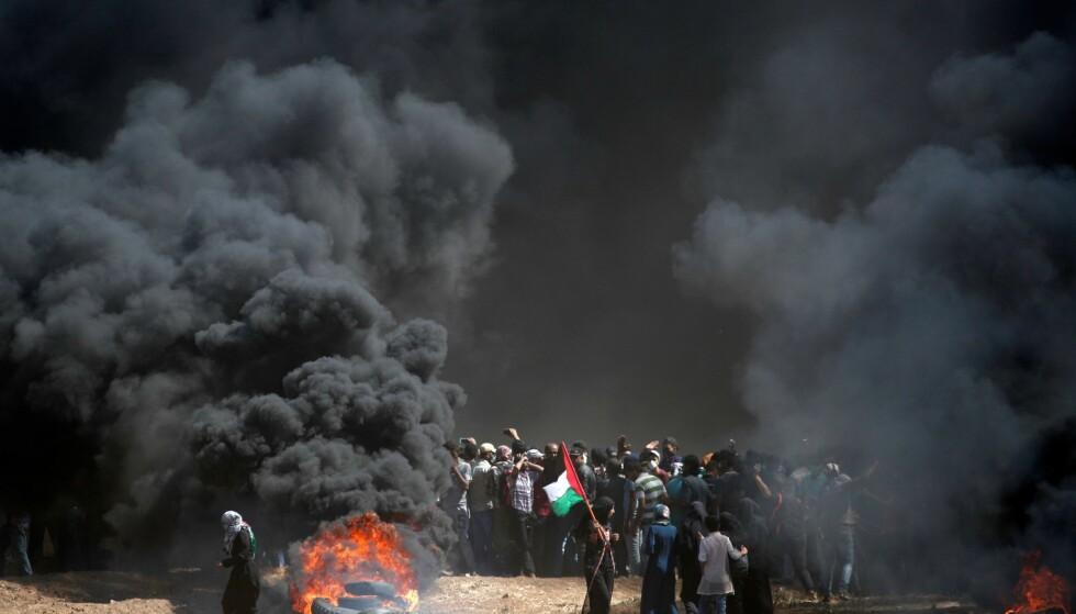 BRENNENDE BILDEKK: En palestinsk demonstrant holder det palestinske flagget under gårsdagens demonstrasjoner. Foto: Scanpix