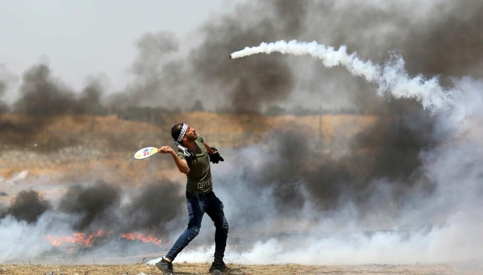 PROTESTER: En palistinsk demonstrant bruker en rackert for å slå tilbake en beholder med tåregass som kommer fra israelske styrker. Bildet ble tatt 11. mai. Foto: APAI Images/Scanpix