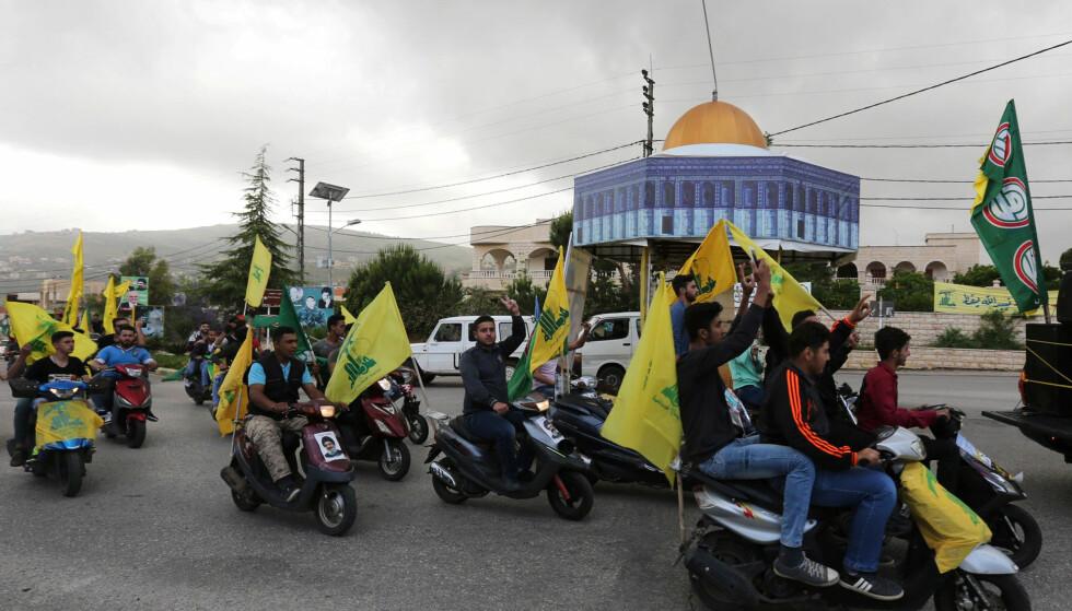 VALGFEIRING: Tilhengere av de sjiamuslimske partiene Amal og Hizbollah kjører rundt i den sørlibanesiske byen Marjayoun dagen etter valget 6. mai. Foto: Aziz Taher/Reuters/NTB Scanpix