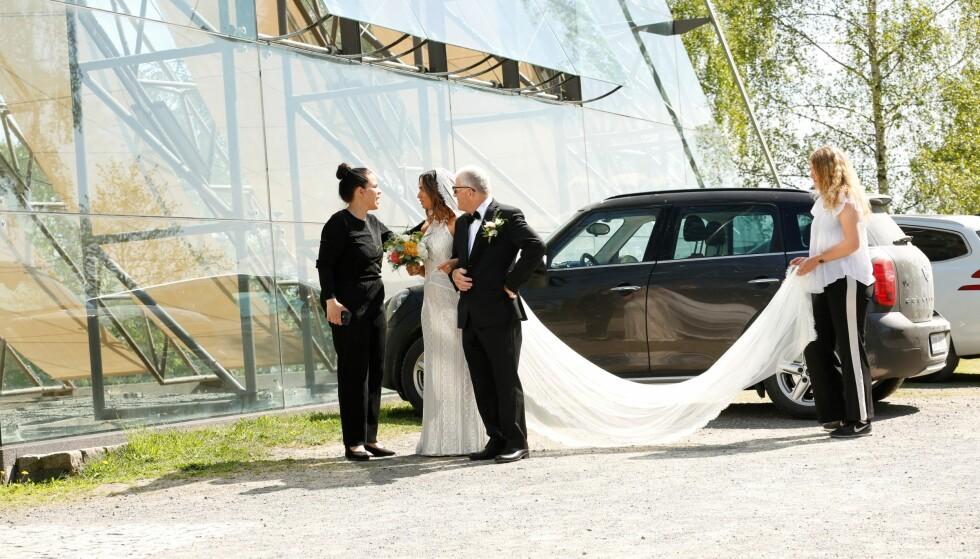 BLONDEKJOLE: Bruden var vakker i en original blondekjole, og bar en fargerik brudebukett på vei inn til vielsen. Foto: Tor Lindseth