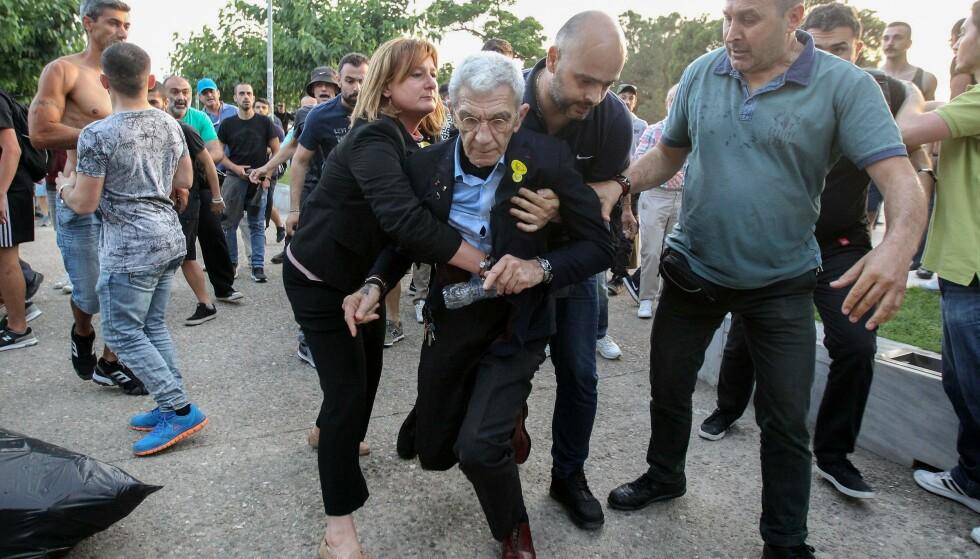 FØRT BORT: 75-årige Yiannis Boutaris måtte føres bort fra et arrangement til minne om grekere som ble drept under og etter første verdenskrig i Hellas' nest største by lørdag kveld, da flere i publikum plutselig ble voldelige. Foto: Eurokinissi / AFP / Scanpix